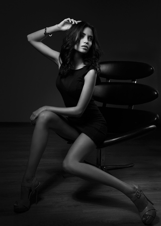 sensual woman: Sexy slim model sitting in fashion armchair and posing in black dress, high heels on dark background. Black and white portrait Stock Photo