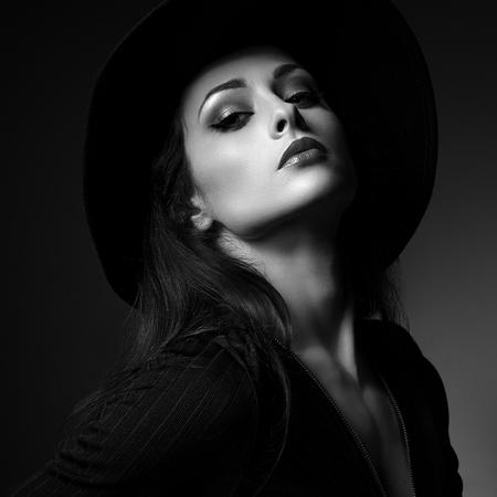 62513188-mujer-atractiva-del-maquillaje-de-glamor-que-presenta-en-sombrero-de-la-moda-en-fondo-oscuro-maquill.jpg?ver=6