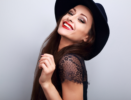 young woman face: Toothy laughing woman in fashion black hat with bright makeup and red lipstick on blue background