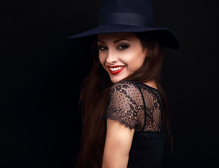 Maquillaje de la mujer feliz en el sombrero de moda azul sonriendo con dientes sobre fondo negro oscuro Foto de archivo