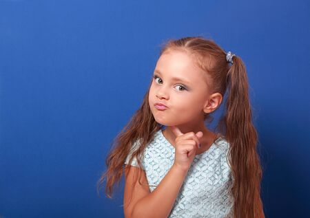 Serious makeup thinking kid girl with long hair looking on blue background with empty copy space Stock Photo