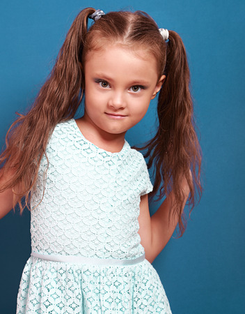 posing: Beautiful makeup kid girl with long hair posing in fashion dress on bright blue background. Closeup portrait Stock Photo