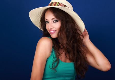 belle brune: Sourire belle jeune femme en chapeau de paille avec de longs cheveux bouclés style de la recherche sur fond bleu. Gros plan portrait lumineux