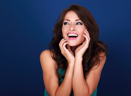 Lachen mooie krullend haar stijl vrouw kijkt met open mond op heldere blauwe achtergrond Stockfoto