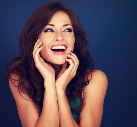 Lachende mooie krullende haarstijlvrouw die met open mond op heldere blauwe achtergrond kijkt. Getoonde portret met lege ruimte