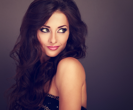 Beautiful bright makeup woman with curly long hair style looking on empty copy space. Toned closeup portrait Imagens