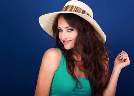Beautiful smiling woman in summer hat with curly long brown hair with manicured nails posing on blue background Stock Photo