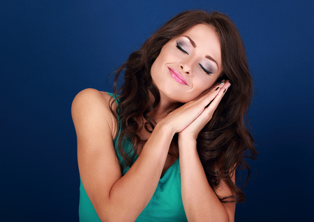 drowse: Beautiful makeup tired young woman want to sleep and she lying on her hands on blue background. Closeup