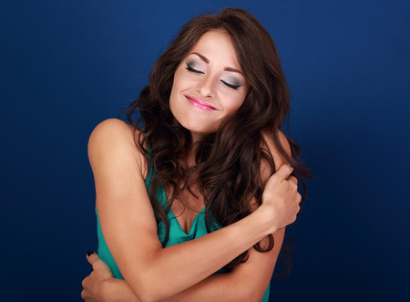 self conceit: Happy makeup woman hugging herself with natural emotional enjoying face. Love concept of yourself body and face on blue background