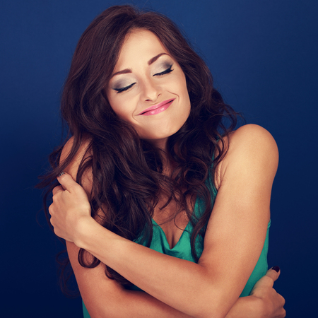 self conceit: Happy makeup woman hugging herself with natural emotional enjoying face. Love concept of yourself body and face on blue background. Closeup Stock Photo