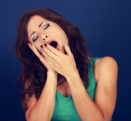 drowse: Beautiful makeup tired woman want to sleep and yawning with manicured hand near mouth on blue background. Toned closeup portrait