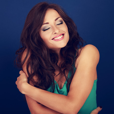 Happy makeup woman hugging herself with natural emotional enjoying face. Love concept of yourself body. Closeup portrait