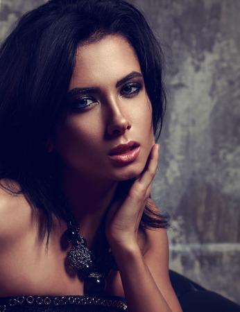 cabello negro: Mujer hermosa maquillaje atractiva con el pelo corto y negro y collar de moda en el cuello en el fondo oscuro. Primer retrato del arte
