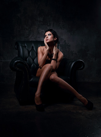 black shadow: Sexy woman in fashion dress posing in luxury black armchair and looking up. Dark dramatic shadow light Stock Photo