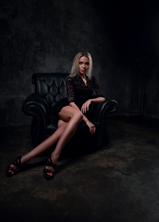 Sexy slim blond model sitting in fashion armchair in black dress and posing on dark shadow background. Drama portrait.