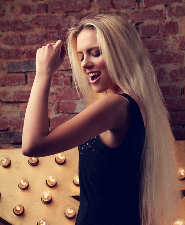beauty girls: Happy dancing young woman singing the song on yellow star and bricks wall background. Toned closeup portrait
