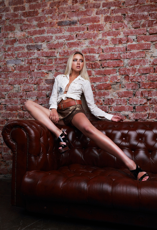 sexy female: Sexy female model posing on the sofa in white shirt and leather shorts and high heels on bricks wall background