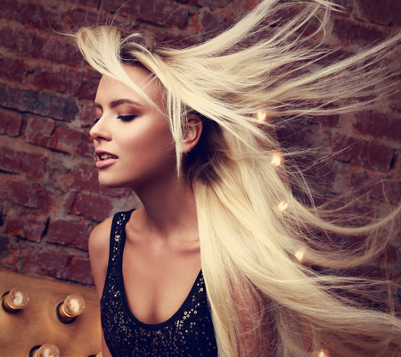 away: Sexy beautiful makeup woman with long blond streaming, fly away hair posing on yellow star and brick wall background. Toned closeup mystic portrait