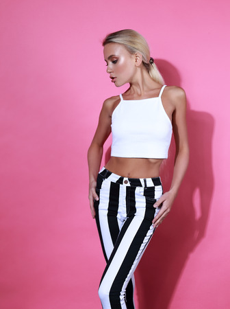 Sexy blond slim model posing in strip trousers and white short top on pink background