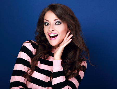 eyes opened: Surprised woman with opened mouth and big eyes holding hand the face and looking happy on blue background
