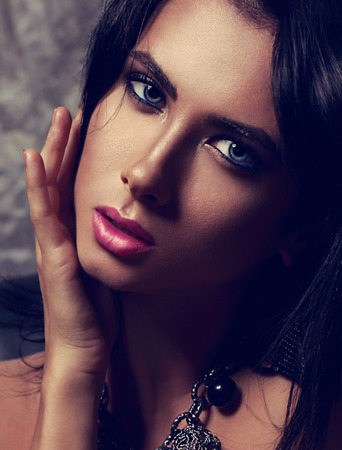 woman portrait: Sexy closeup portrait of evening makeup woman with bright blue eyes, eyeliner and pink hot lips looking passion. Toned contrast portrait Stock Photo