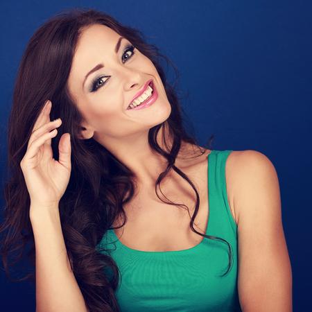 Hermosa mujer feliz estilo de pelo rizado que mira con sonrisa sobre fondo azul. Retrato del primer