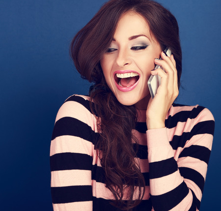 screaming: Happy excited woman talking on mobile phone with wide opened mouth on blue background Stock Photo