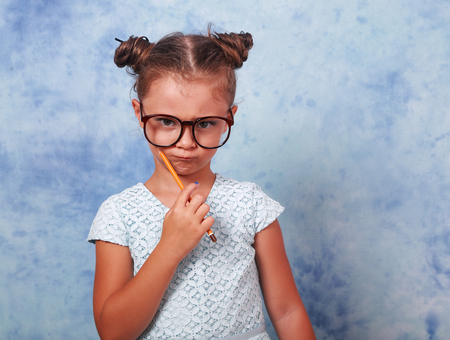 rigorous: Serious strict kid girl in eye glasses holding pencil and thinking about with trendy hair style on blue background