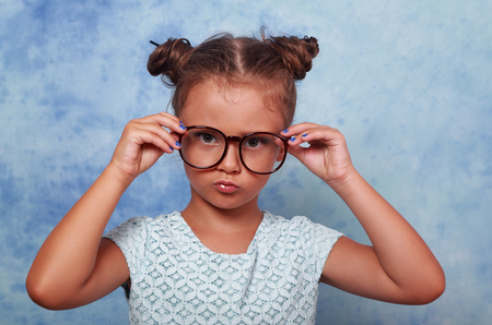 Serious angry kid girl with modern hair style in fashion glasses looking and holding the eyeglasses with empty copy space background. closeup portrait Zdjęcie Seryjne