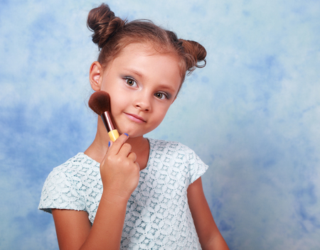 Cute beautiful small kid girl applying tonal cosmetic on the face using makeup brush with happy smile on blue background Stock Photo