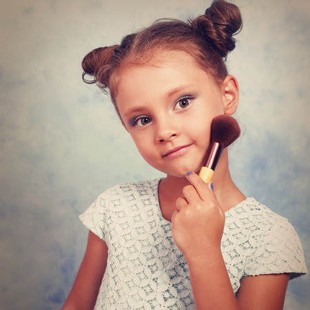 Cute beautiful small kid girl applying tonal cosmetic on the face using makeup brush with happy smile. Toned portrait. Closeup