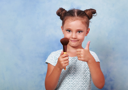 tonal: Beautiful small kid girl applying tonal cosmetic brush and showing thumb up sign on blue background with empty copy space Stock Photo