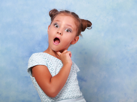 Funny surprising and very excited kid girl looking in camera on blue background