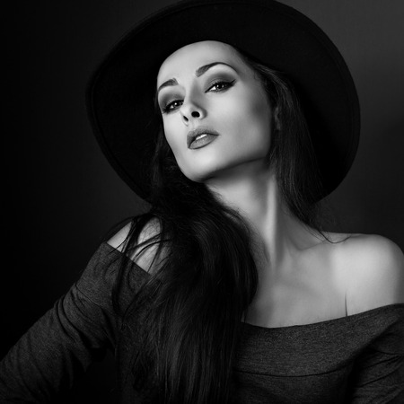 Sexy elegant makeup woman in fashion hat posing on dark shadow background. CLoseup portrait. Black and white