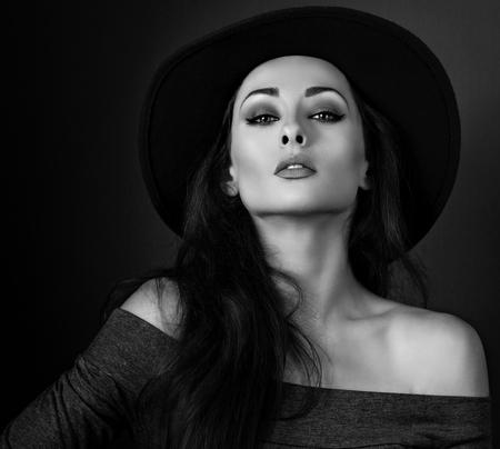 black shadow: Expressive makeup woman in fashion elegant hat posing on dark shadow background. CLoseup portrait. Black and white portrait