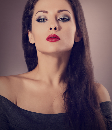 ceremonial make up: Beautiful woman with bright smokey makeup eyes and red lipstick. closeup make-up. Toned portrait