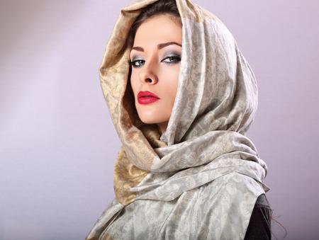 빨간 립스틱 스튜디오에서 머리 덮여 동양 전통 목도리와 함께 포즈를 가진 아름 다운 메이크업 여성