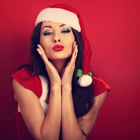 red lips: Fun happy woman showing kissing sign with hands at face in christmas costume on red background. Bright closeup portrait
