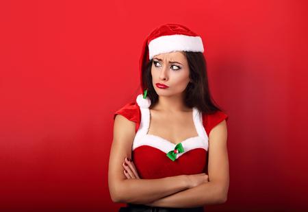 Mujer infeliz ofendida en problemas con los brazos cruzados en el espacio de copia vacía en traje de Navidad sobre fondo rojo