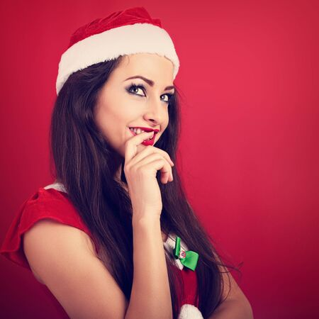 Flirting coquette woman in santa claus christmas costume looking up with finger at lips on red background with empty copy space. Closeup Stock Photo