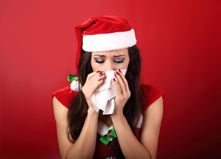 blowing nose: Flu. Unhappy frustration sick woman holding paper tissue near her nose and looking down in christmas night on red background