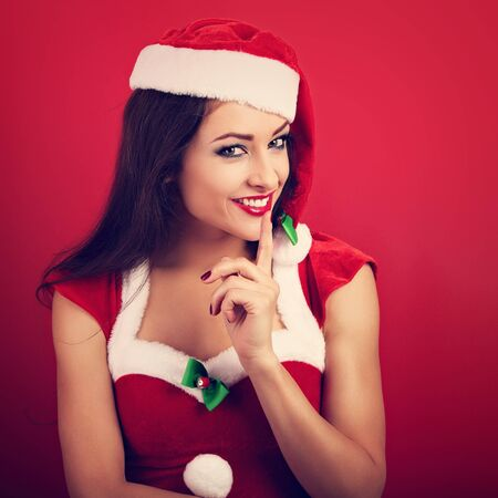 silencio: Beautiful woman with toothy smile in santa claus christmas costume showing the finger the silence sign on bright red background. Closeup portrait
