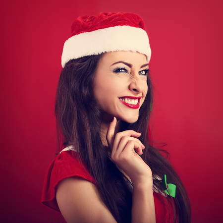 Fun squint excited grimacing woman in santa claus christmas costume looking up on bright red background with empty copy space. CLoseup portrait