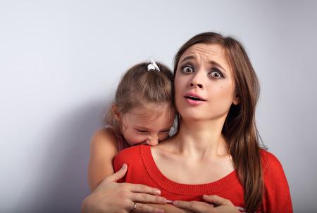agotado: Enojado muchacha niño emocional con ganas de morder y terroring su madre asustada bushed sorprendido con grandes ojos en el fondo azul. Humor retrato concepto Foto de archivo