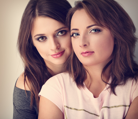 tenderness: Two beautiful calm girl friends looking with love and natural tenderness emotion. Toned closeup portrait