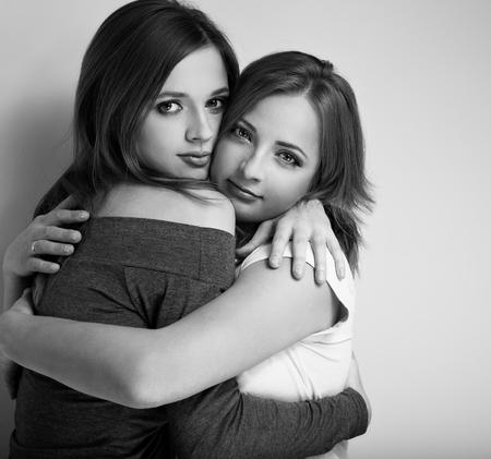 amigos abrazandose: Dos hermosas jóvenes amigos tranquilidad emocional abrazan con amor y mirando tierna. Primer retrato en blanco y negro Foto de archivo