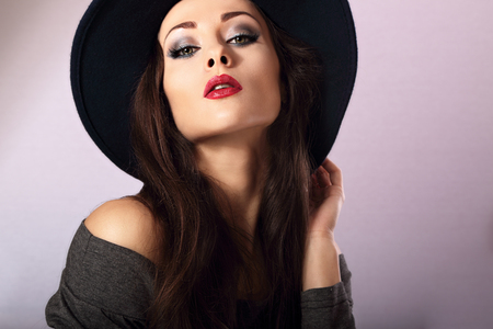 sexy female: Sexy female model with bright makeup and red lipstick in black hat posing. Closeup fashion portrait