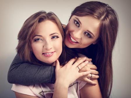 anillo de boda: Dos amigos hermosa de risa de muchacha que abrazan con amor con los anillos en los dedos. Retrato de detalle. tonificado