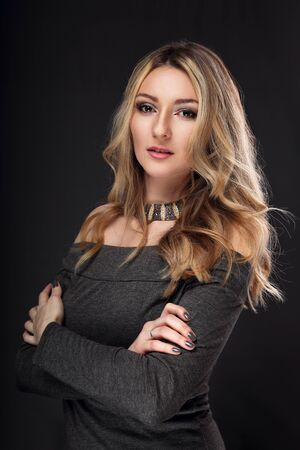 folded: Fashion success business blond woman with folded arms looking serious on dark background