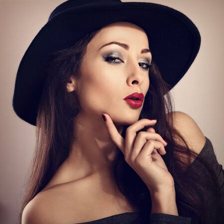 smoky black: Expressive female model with bright makeup and red lipstick, manicured nails posing in black hat. Closeup fashion portrait. Toned portrait